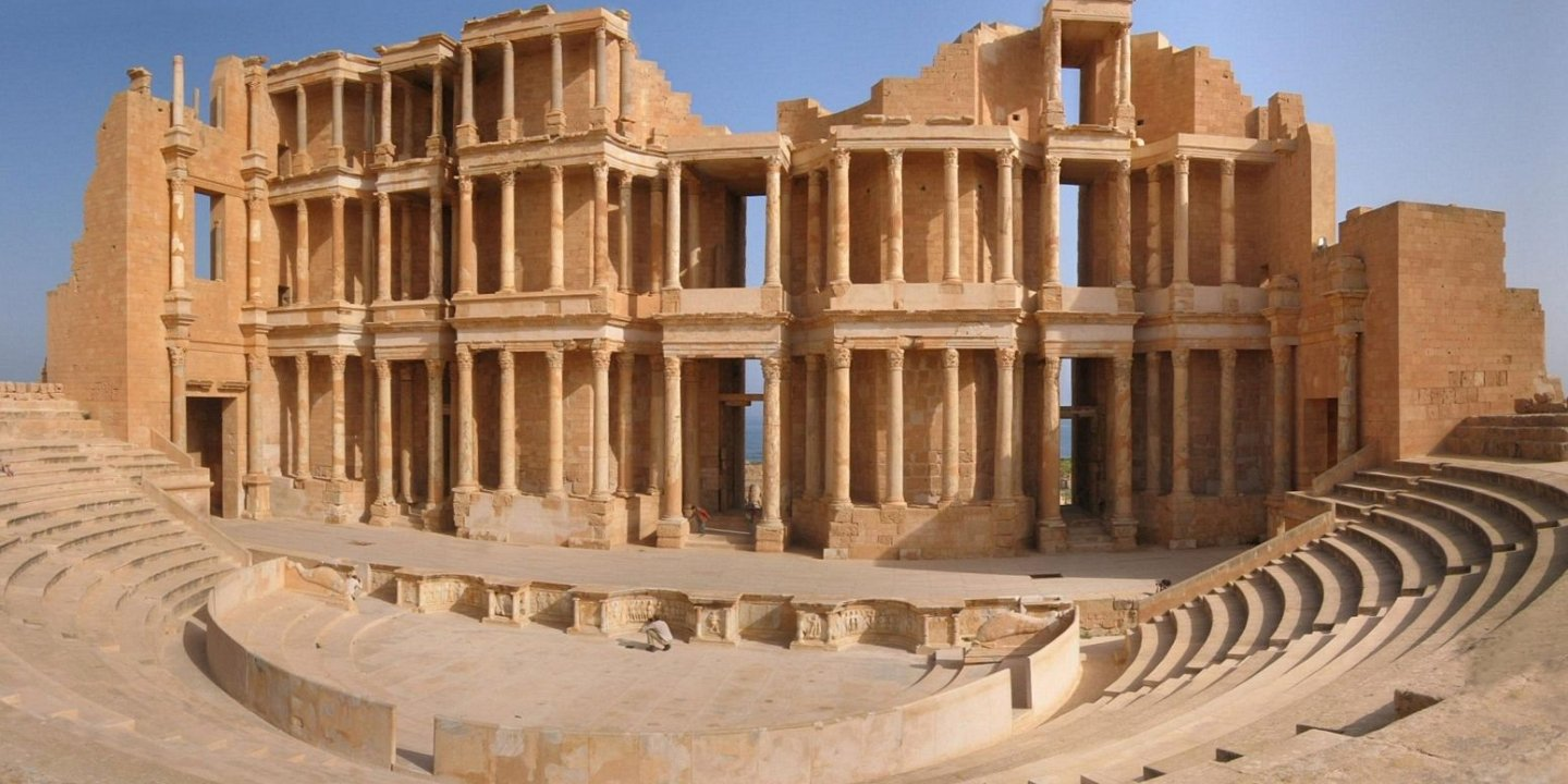 Sabratha lies to the North West of Libya on the coast with spectacular sea views. This city has been declared a UNESCO World Heritage Site with it's trade port dating back to 500BC. The city today is ruins, but there are temples, a magnificent third century theater, a forum and so much more to see, giving you a true idea of the size of this once very busy port town in North Africa. The city was rebuilt after an earthquake struck the area in the fourth century, but took a rapid decline in the fifth century thanks to the Vandal misrules of the area. Soak Up The History Walking around Sabratha, you are able to soak up the history and culture of this once thriving port town. Take a walk through the stunning theater, a large part of this structure still stands today with it's impressive columns and arches adorned in beautiful artwork. Stop in at the Forum surrounded by crumbling walls. Take note of the decorative and inscribed pillars, monuments and fabulous mosaics. See the mosaics of the House of Jason Magnus, this is one of the many monuments standing for you to explore when visiting this port town of Sabratha. There is a host of temples, many lie in ruins, but you are still able to make out the magnitude of these once magnificent structures from the Isis Temple and Serapis Temple to the Liber Pater Temple and Antonine Temple. The Baths sit on the cliff edge overlooking the ocean offering spectacular sea views. The sandstone blocks complete with the magnificent mosaics show the beauty that the people once absorbed while enjoying what the baths had to offer. Before you leave stop in at the Museum of Sabratha which opened in 1932. Walk through the choice of galleries brimming with historical artifacts including mosaics and statues.